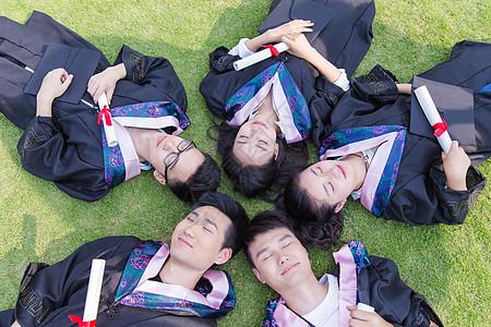 毕业季大学生们躺草地拿着证书图片
