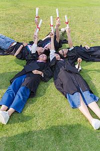 毕业季大学生们躺草地举着证书图片