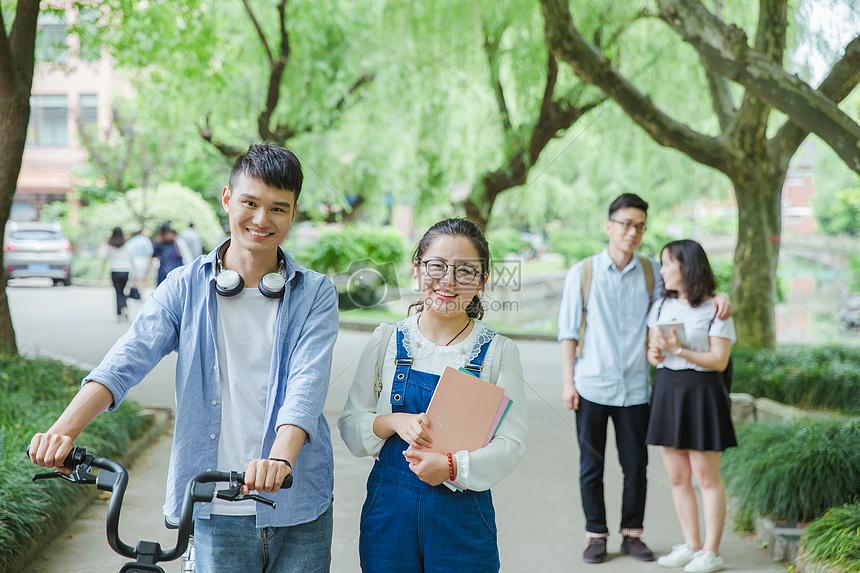青春大学生推自行车散步聊天