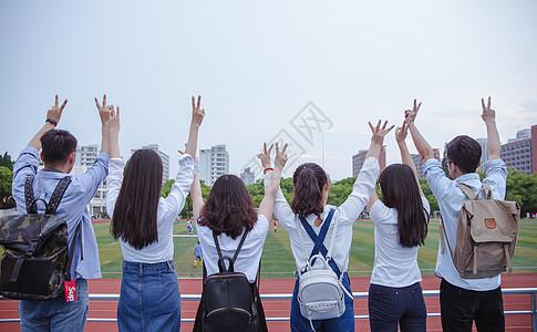 毕业季操场上青春大学们举手比耶图片