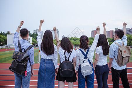 操场上青春活力大学们举手握拳图片
