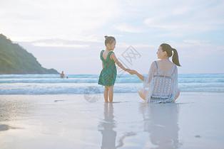 海边牵手的母子背影图片