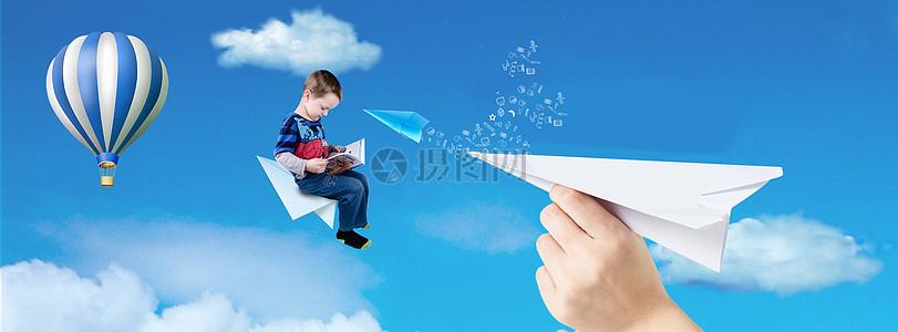 坐在纸飞机上看书的男孩图片