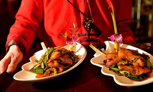 双手端着四川名菜回锅肉上菜图片
