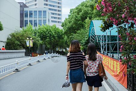校园路上两个女孩挽手散步图片