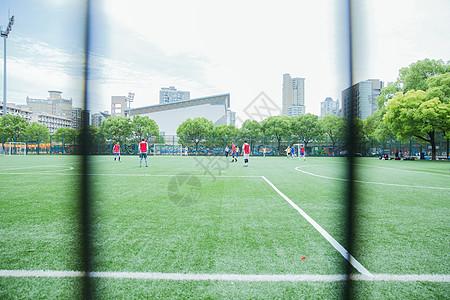 校园阳光足球场老人在踢球图片