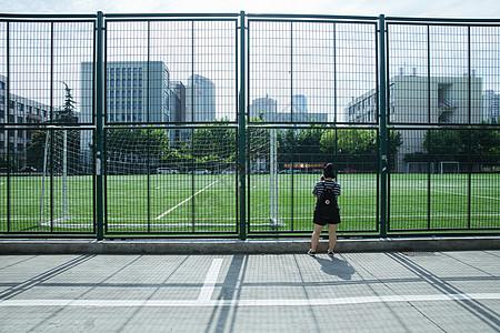 校园阳光足球场女孩在拍照背影图片