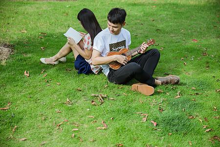 校园男女草地上弹乐器看书图片