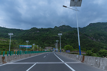 多云天气大气依山隧道前公路图片
