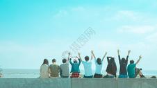 毕业季海边欢快人群背影图片