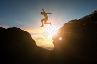 从山峰上跳跃的男人图片