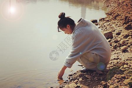 夕阳西下河边美女溪水潺潺落日阳光镜头光晕图片