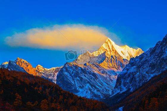 夏诺多吉雪山的日照金山和飘动的云图片
