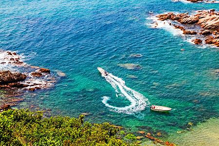 蓝绿色的海滩红橙色的礁石和开动的快艇激起的浪花图片