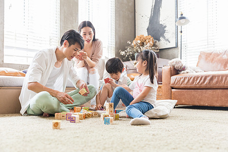 年轻父母陪孩子在客厅搭积木图片