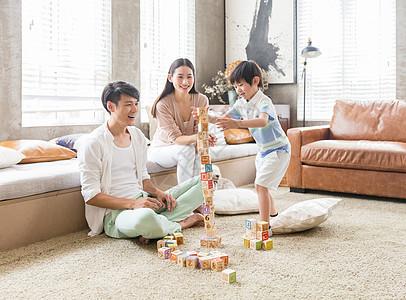 年轻父母陪孩子在家玩游戏图片