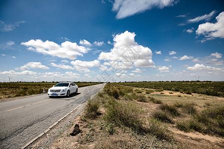 草原的公路上飞驰的车图片
