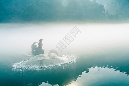 渔夫在起雾的江中撒网打鱼图片