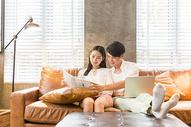 年轻情侣沙发休闲放松阅读图片