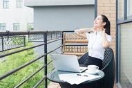 美丽职业女性阳台伸懒腰图片