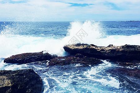 雪白的海浪拍打在礁石上图片