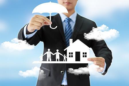 商务男士手握雨伞房屋人白云图片