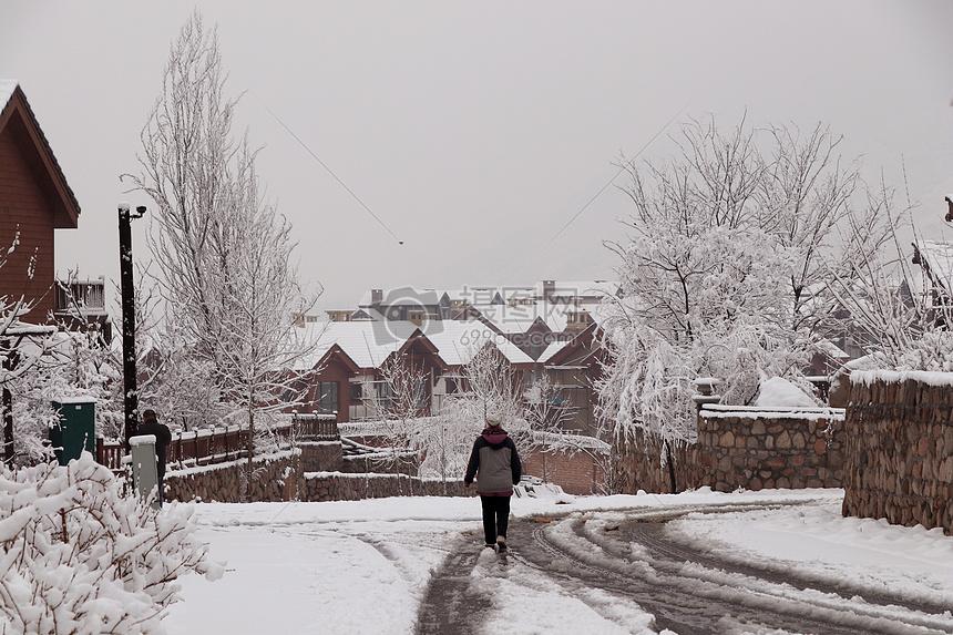 早晨雪地里的建筑与行路人图片