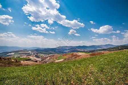 云南东川红土地-蓝天白云红色山丘图片
