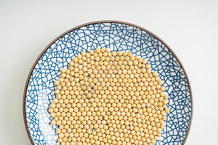 黄豆散落在盘子上图片