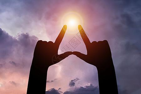 夕阳的背景上的我爱你的手影图片