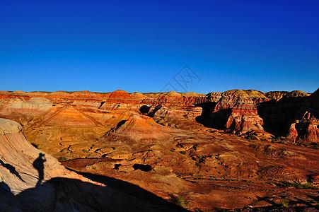 新疆五彩城夕阳下的彩色山丘与摄影师剪影图片