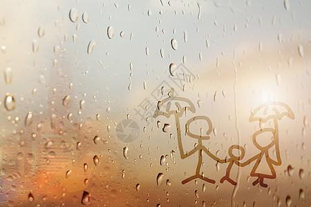 玻璃窗上雨滴的家庭图片