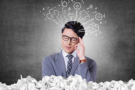 在纸堆中思考的男人图片