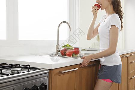 厨房里吃新鲜水果的女孩图片