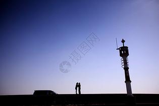 海边灯塔边有一对情侣在恋爱图片