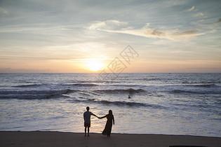 情侣在夕阳西下的海边看大海图片