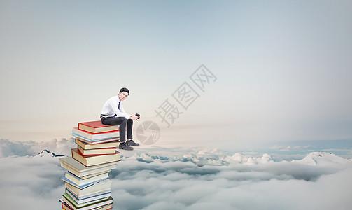 坐在书上的商务人士图片