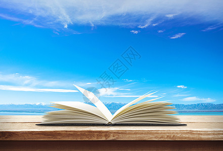 蓝色天空下展开的书本图片