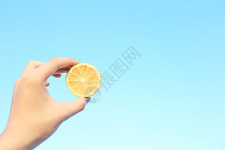 夏日蓝天下手举柠檬图片