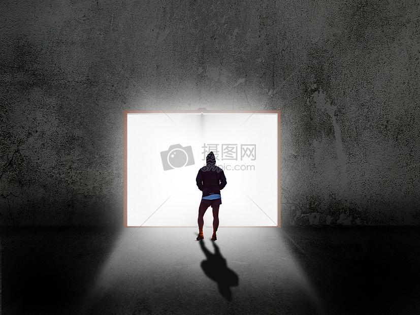 男子站在发光书前图片
