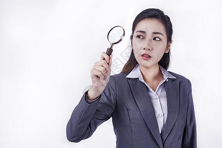 职业女性手拿放大镜寻找图片