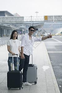 男女情侣在机场拉着拉杆箱叫车图片