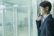 商务男士在机场大厅落地玻璃前用电话通讯图片