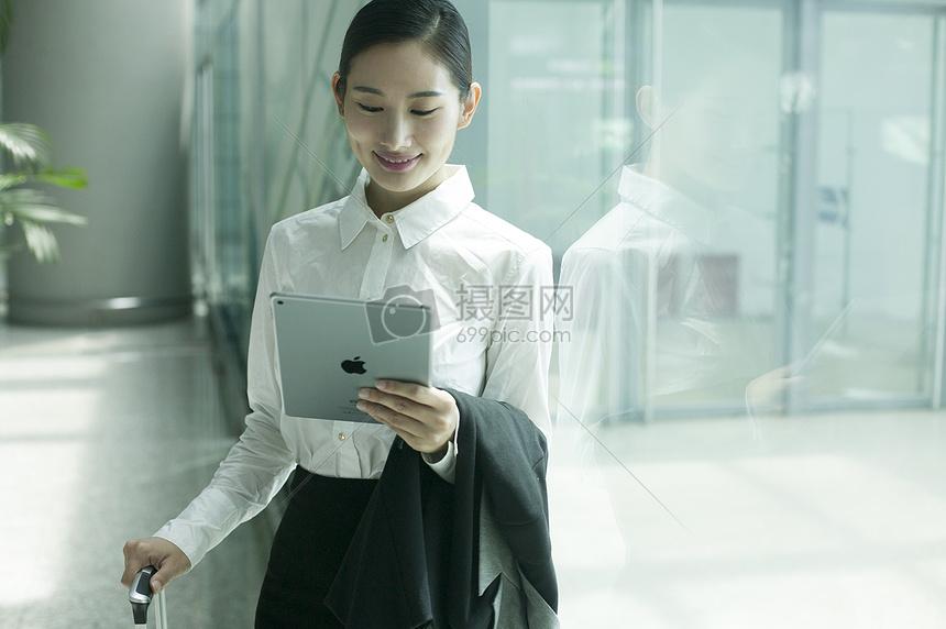 商务女士在机场大厅手提拉杆箱看着ipad图片