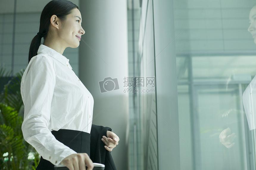 商务女士在机场大厅看着户外图片
