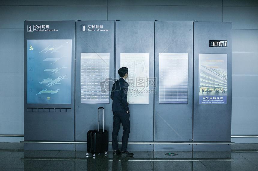 商务男士手提拉杆箱在机场时刻表上看时间图片