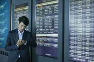 商务男士手提拉杆箱在机场时刻表前看时间图片