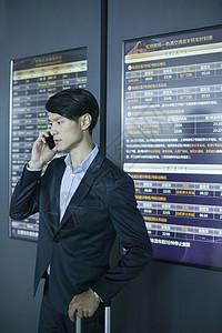 商务男士在机场时间表前用手机通话图片