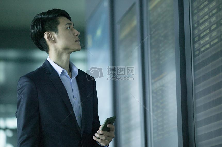 商务男士在机场时刻表前拿手机观察图片
