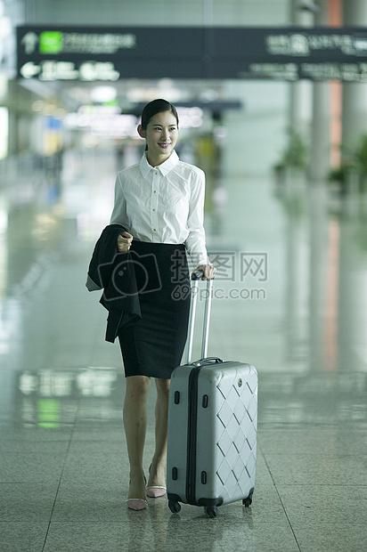 商务女士手提拉杆箱从机场大厅经过图片